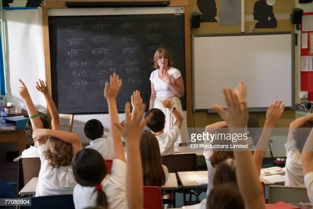 Multi-ethnic children with hands raised in class