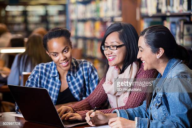Multi-ethnic college students study in library