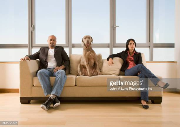 Multi-ethnic couple and dog sitting on sofa