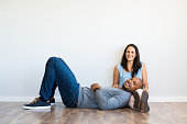 Young multiethnic couple relaxing on floor and looking at camera with copy space. Happy african man resting on the leg of his girlfriend after move house. Black guy lying on ground with her wife in ne