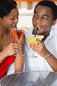 Multi-ethnic couple drinking cocktails