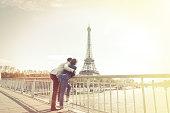 Multi-ethnic couple enjoying their trip to Paris along the Seine river, near Eiffel Tower.
