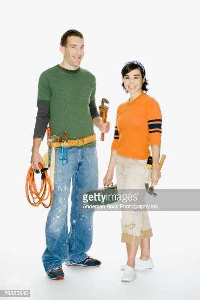 Multi-ethnic couple holding tools