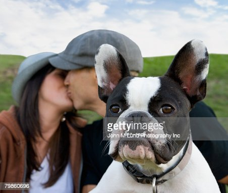 Multi-ethnic couple kissing behind dog : Stock Photo