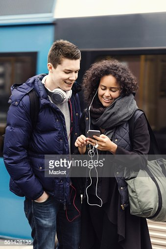 Multi-ethnic couple listening music through mobile phone on subway platform