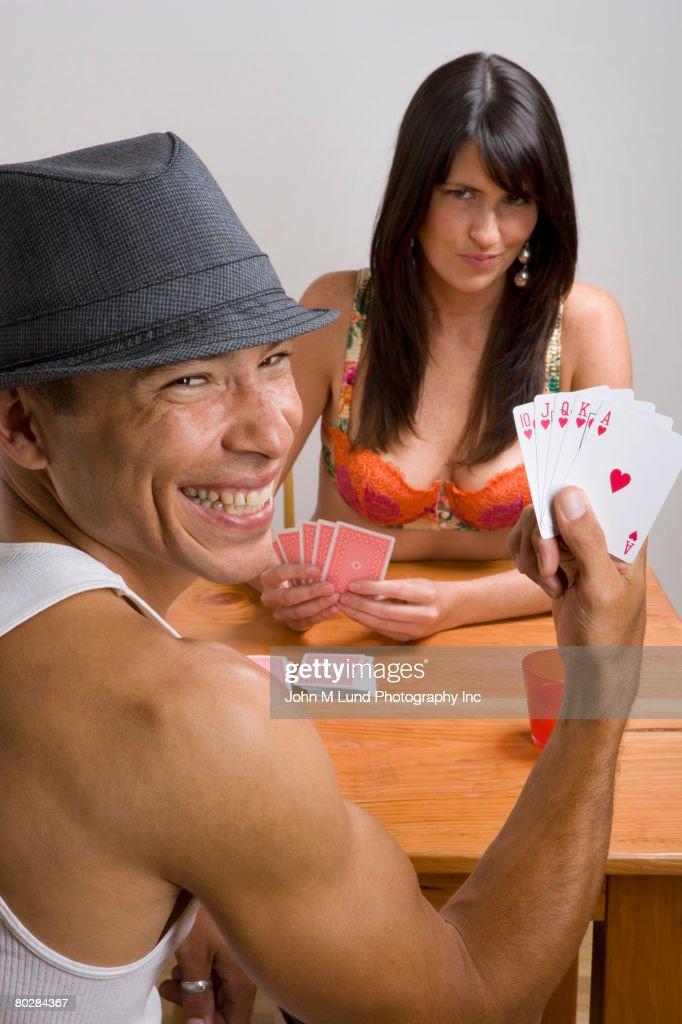 Multi-ethnic couple playing strip poker : Stock Photo