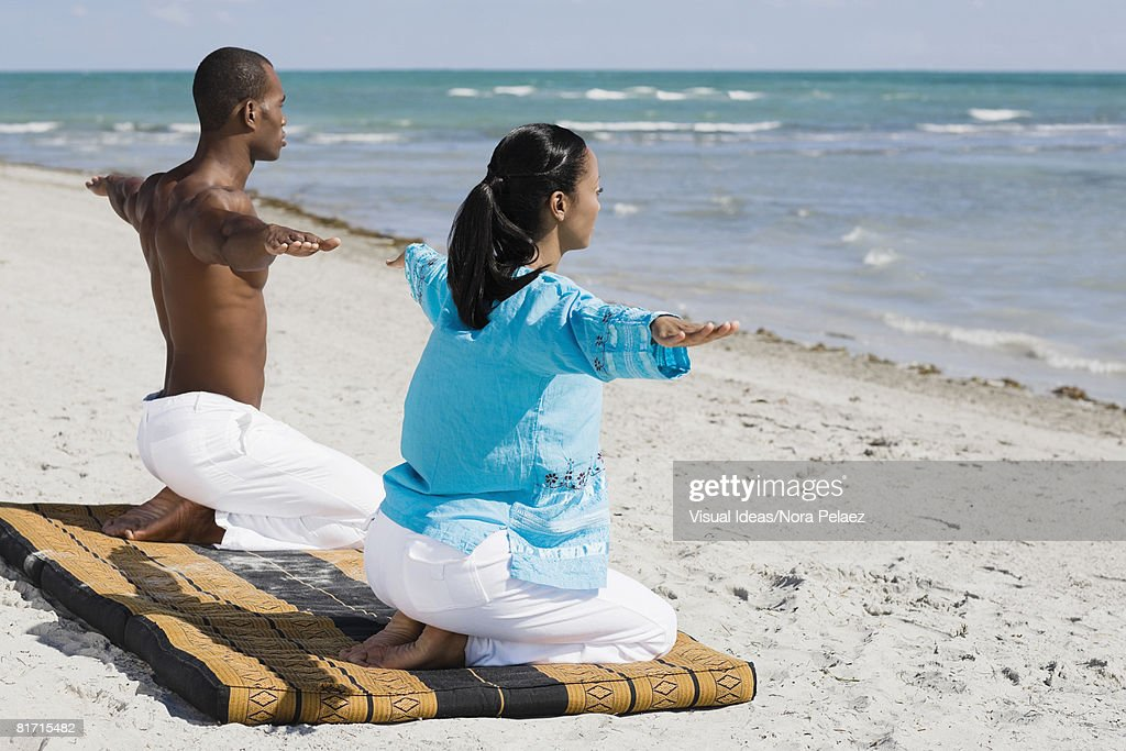 Multi-ethnic couple practicing yoga : Stock Photo
