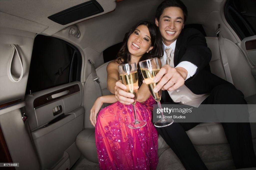 Multi-ethnic couple toasting in limousine : Stock Photo
