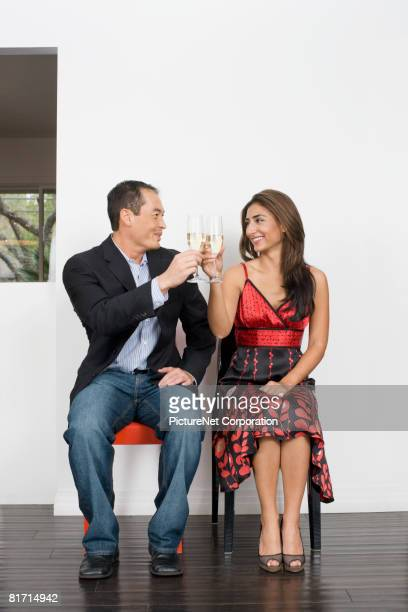 Multi-ethnic couple toasting with champagne