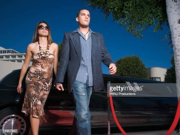 Multi-ethnic couple walking away from limousine