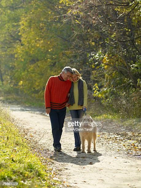 Multi-ethnic couple walking dog