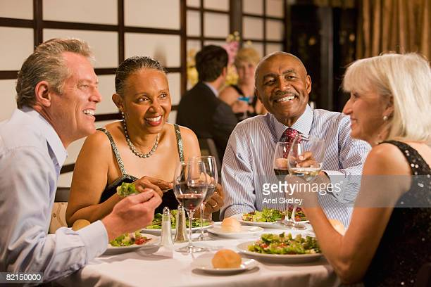 Multi-ethnic couples eating at restaurant