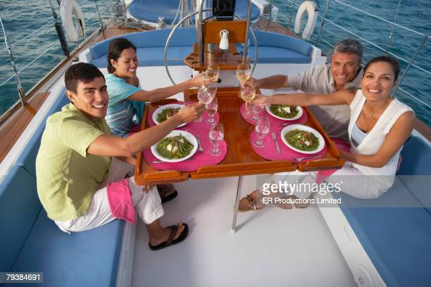 Multi-ethnic couples eating on sailboat