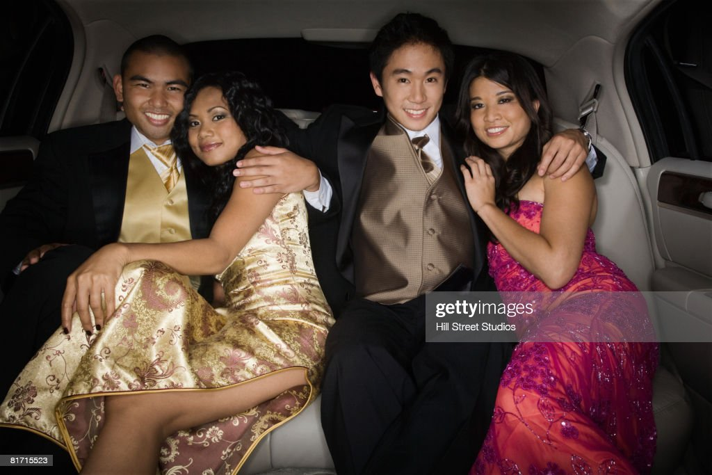 Multi-ethnic couples hugging in limousine : Stock Photo