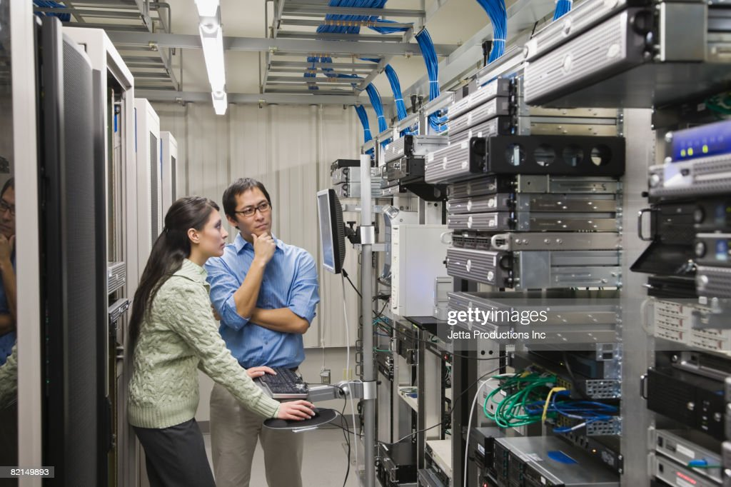 Multi-ethnic coworkers working in computer server room