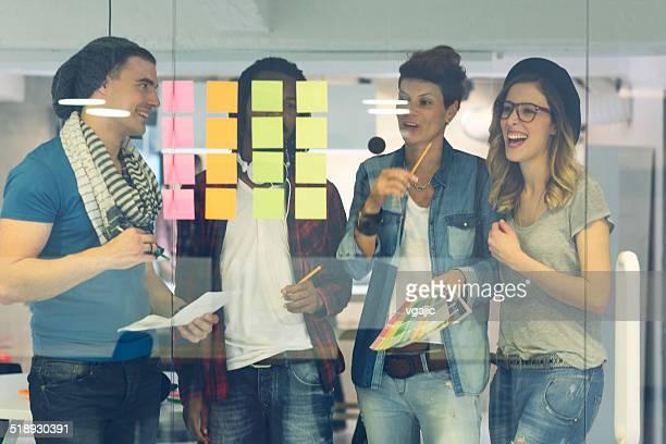 Multiétnico equipo creativo mirando en notas adhesivas y escrito.