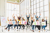 Multiethnic diverse group of happy business people cheering together, celebrate project success with papers written We did it. Coworker teamwork, team achievement, or small business startup concept