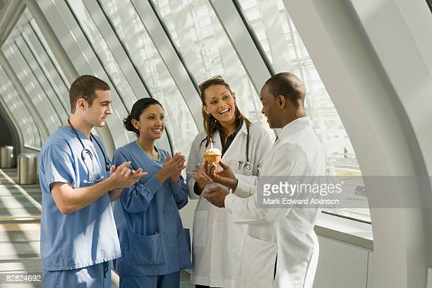 Multi-ethnic doctor and nurses giving doctor birthday cupcake