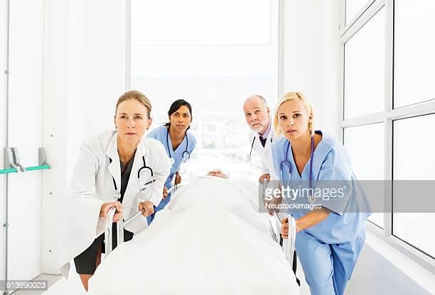 Diversité ethnique médecins et infirmières en poussant Patient sur La civière