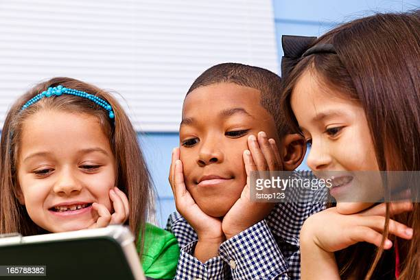 Multi-ethnic elementary 7-year-old children. Digital tablet. School, education. Technology.