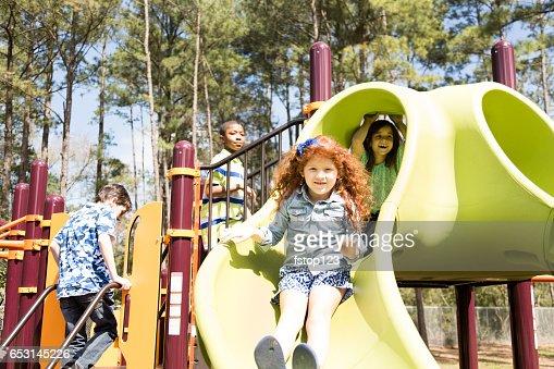 Multi-ethnic elementary school children playing on playground at park. : Stock Photo