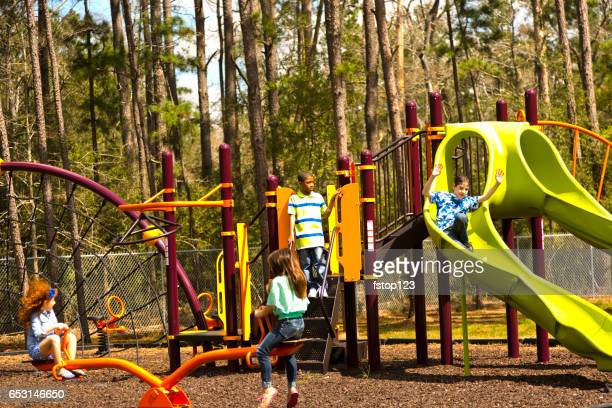 Multi-ethnic elementary school children playing on playground at park.