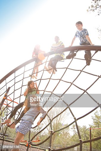Multi-ethnic elementary school children playing on playground at park. : Bildbanksbilder