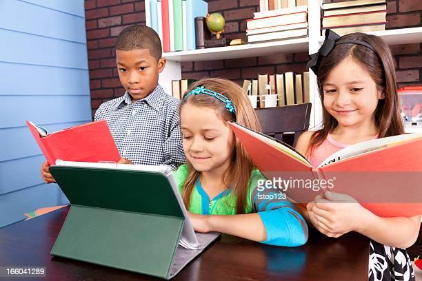 Multiétnico elemental estudiantes. Escuela montaje tipo aula. Tableta Digital y libros.