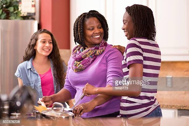 Multi-ethnique de maison familiale de cuisson ensemble dans la cuisine.