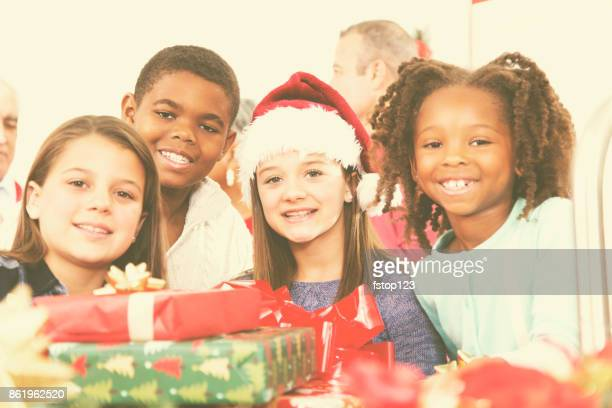 Multi-ethnic family, children in home kitchen at Christmas party.