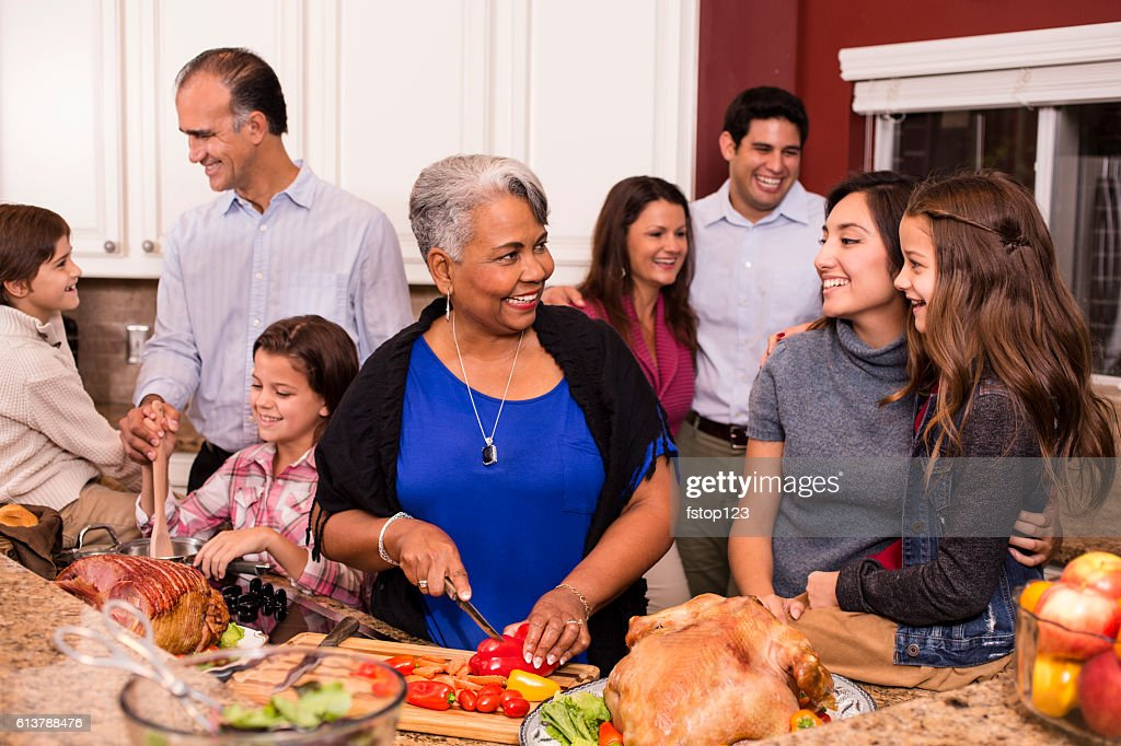 Multi-ethnic family cooks Thanksgiving, Christmas dinner in grandmother's home kitchen. : Stock Photo
