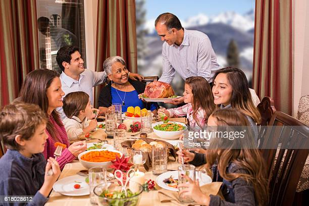 Multi-ethnic family enjoying Christmas dinner at grandmother's home.