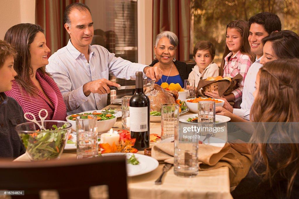 Multi-ethnic family enjoying Thanksgiving dinner at grandmother's home. : Stock Photo