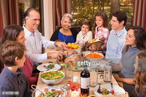 Multi-ethnic family enjoying Thanksgiving dinner at grandmother's home. : Foto de stock