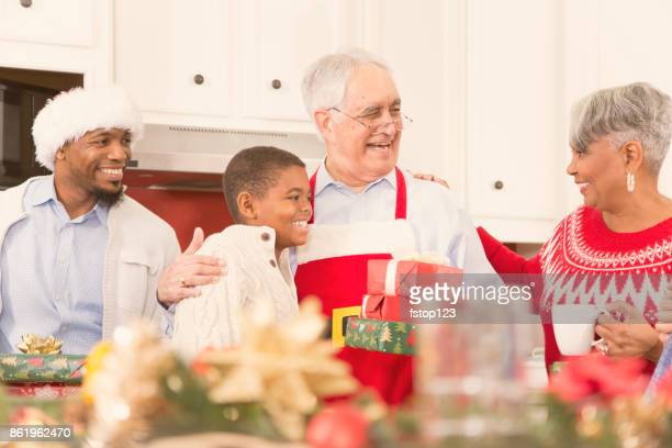 Multi-ethnic family in home kitchen at Christmas party.