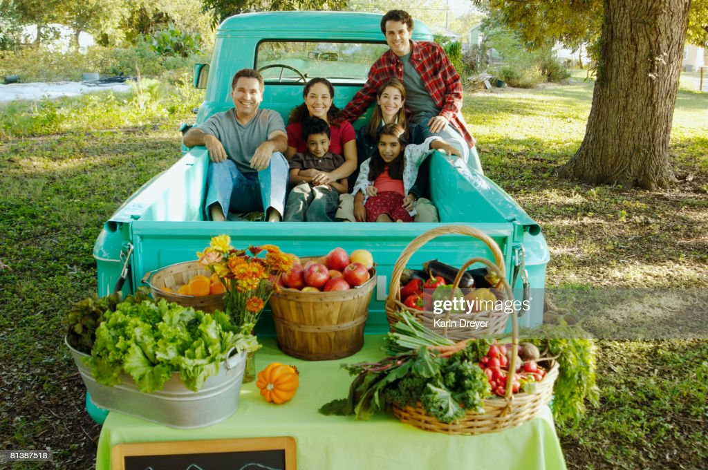Multi-ethnic family in truck at farm stand : Stock Photo