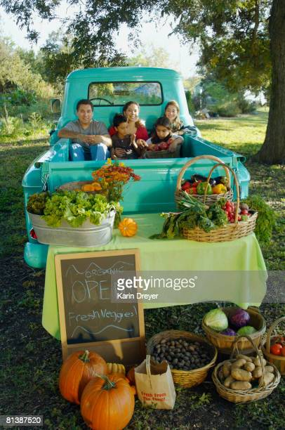 Multi-ethnic family in truck at farm stand