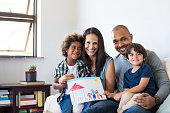 Proud parents showing family painting of son sitting on sofa at home. Smiling mother and father with children'u2019s drawing of a new home. Black little boy with his family at home showing a painting