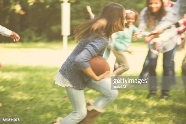 Multi-ethnic family playing football in backyard at Thanksgiving.