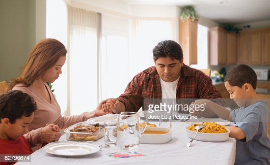 Multiethnic Family Praying At Dinner Table Stock Photo ...