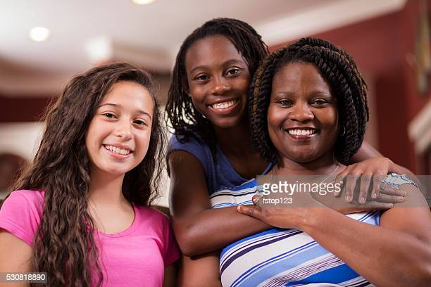 Multi-ethnic family.  Teenage girls and mom at home.  Hugs.