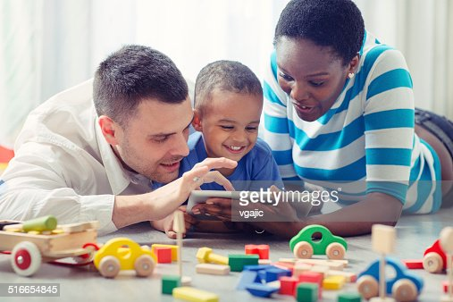 Multi-ethnic Family with one child having fun with digital tablet.