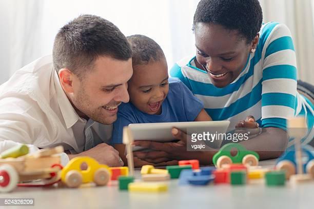 Multi-etnico famiglia con un bambino che si diverte con digital tablet.