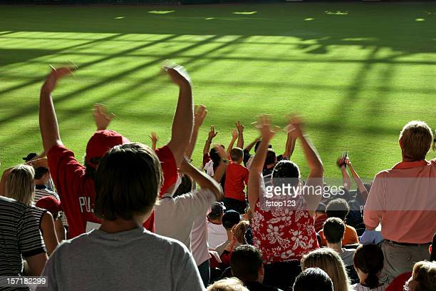 Multi-ethnic fans standing, cheering in stands. Baseball, soccer stadium.