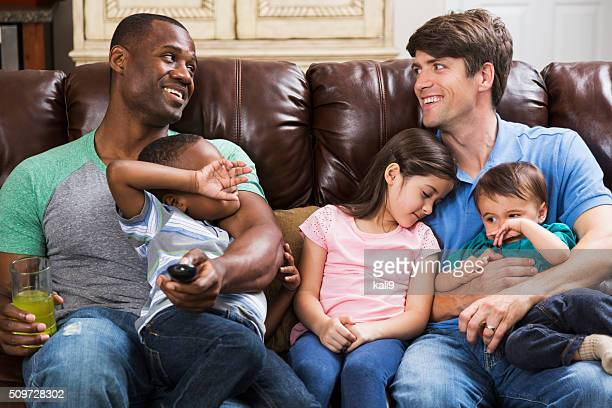 Multi-ethnic fathers with children on couch watching TV