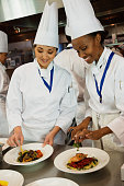 Multi-ethnic female chefs garnishing plates of food