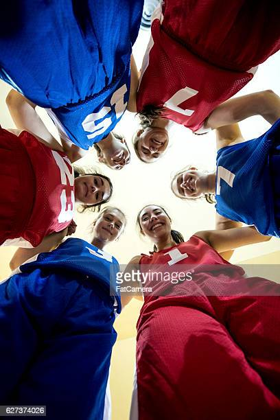Multi-ethnic female high school basketball team during a huddle