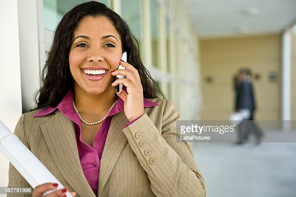 Multi-ethnic female holding plans and talking on phone