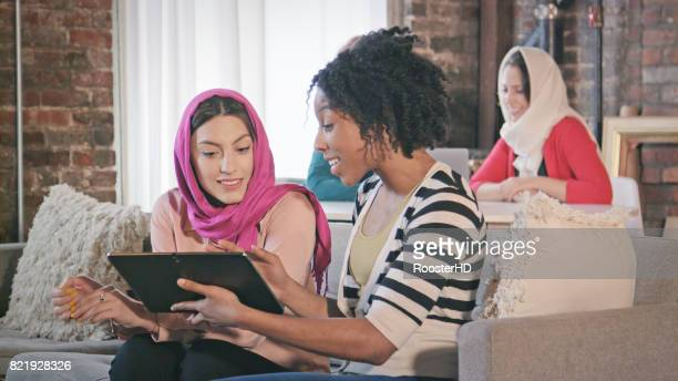 Multi-Ethnic Female Professionals Interact with Digital Tablet