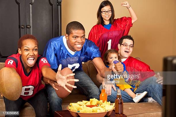 fan di calcio multietnico di amici. Casa guardando la partita in televisione.